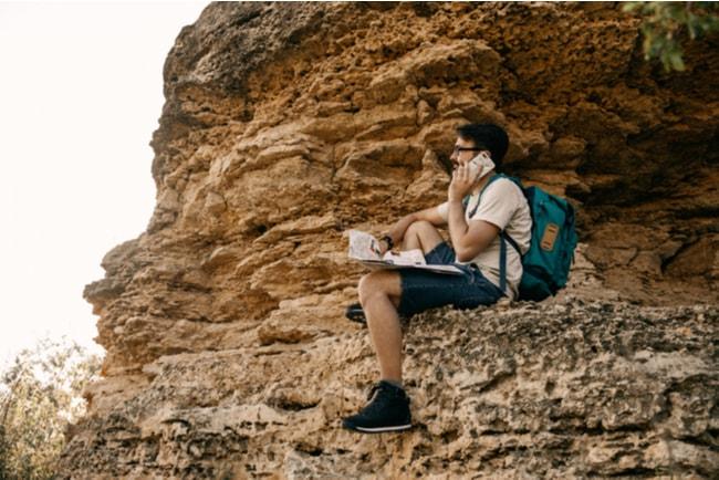 ung man sitter på klippavsats med mobil och karta