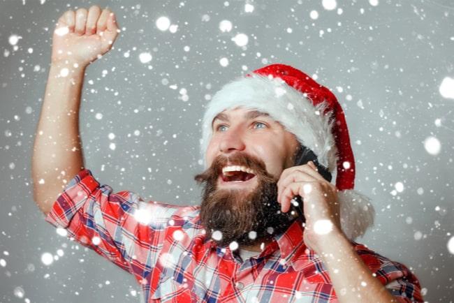 man med tomteluva står i snöfall och pratar i mobil och höjer handen i segergest