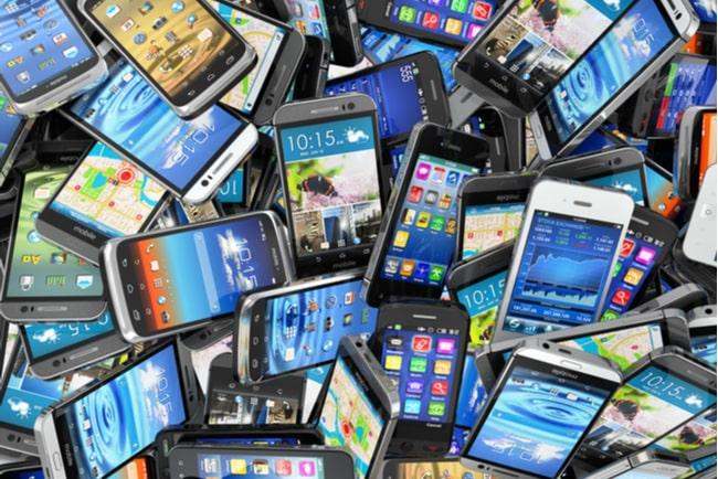 en hög med begagnade mobiltelefoner