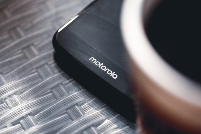 närbild på motorola-mobil bredvid en kopp kaffe i förgrunden
