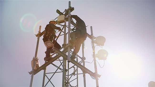 byggarbetare uppe i en mobilmast
