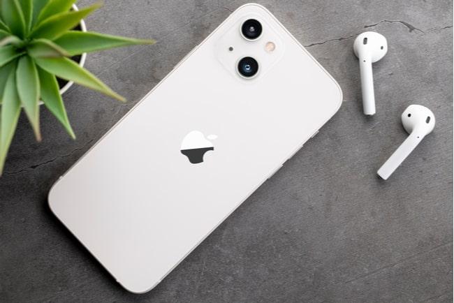 En vit iphone 13 ligger på grått bord med hörlurar på sidan.